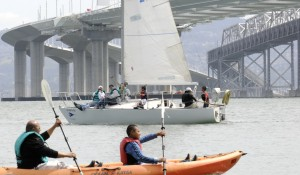 paddle and sails framed by bridge